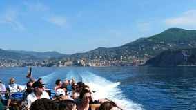 Tour speed boat people Camogli horizon. Italian Riviera, Italy, 29 April 2018 - People during a tour on speed boat that leave trail in the Italian Riviera`s stock video footage