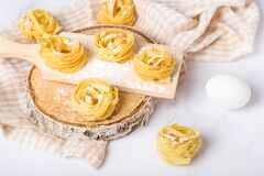 Italian rolled fresh fettuccine pasta with flour on white background