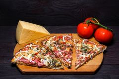 Italian rustic pizza, three pieces on a wooden tray, dark wooden table, with tomatoes and cheese stock photography