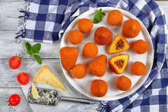 Italian saffron risotto cone and balls. Sicilian arancini - saffron risotto cone and balls stuffed with meat ragu and green peas on platter on wooden table with Royalty Free Stock Photos