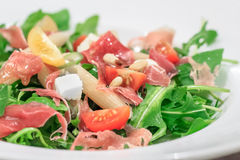 Italian salad with prosciutto and arugula. Salad with prosciutto, tomatoes, pasta, basil, pine nuts and arugula Royalty Free Stock Photo