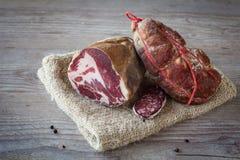 Italian salami assortment. Assortment of tasty italian salami on wooden background Royalty Free Stock Photo