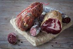 Italian salami assortment. Assortment of tasty italian salami on wooden background Royalty Free Stock Image