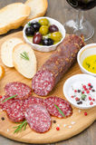 Italian salami, bread, olives and spices on a cutting board Royalty Free Stock Photos