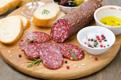 Italian salami, bread and spices on a cutting board Stock Image