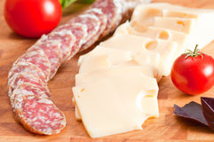 Italian salami, cheese and tomatoes. Focus on foreground Stock Images