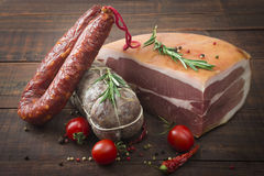 Italian salami, prosciutto ham and spicy sausage with cherry tomatoes and red pepper and spices Royalty Free Stock Photography