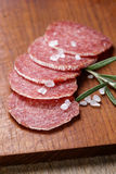 Italian salami sausage slices with rosemary and sea salt Royalty Free Stock Photos