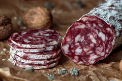 Italian salami with walnuts. On craft paper on rustic wooden background royalty free stock photos
