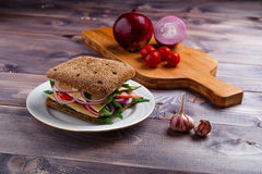 Italian sandwich. With red onion, cherry tomatoes, green salad, ham and cheese Royalty Free Stock Images
