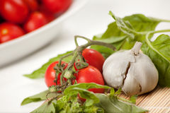 Italian Sauce Ingredients. Garlic basil and cherry tomatoes on a white background Royalty Free Stock Photo