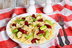 Italian Sausage Bowtie Pasta warm salad with avocado slices Stock Image