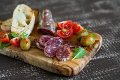 Italian sausage, ciabatta, olives and cherry tomatoes in olive Board Royalty Free Stock Photo