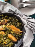 Italian sausages with rapini broccoli in a skillet. With table setting on green wooden table royalty free stock photos