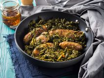 Italian sausages with rapini broccoli in a skillet. With table setting on green wooden table royalty free stock image