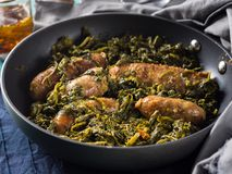 Italian sausages with rapini broccoli in a skillet. With table setting on green wooden table royalty free stock photography