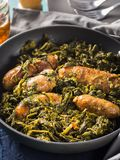 Italian sausages with rapini broccoli in a skillet. With table setting on green wooden table stock images