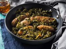 Italian sausages with rapini broccoli in a skillet. With table setting on green wooden table stock photography