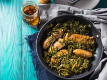 Italian sausages with rapini broccoli in a skillet. With table setting on green wooden table stock image