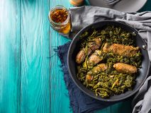 Italian sausages with rapini broccoli in a skillet. With table setting on green wooden table stock photo