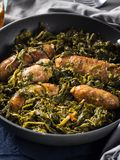 Italian sausages with rapini broccoli in a skillet. With table setting on green wooden table stock photos