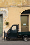 Italian scene with ape car. Italian car parked in front of a yellow building with stock images