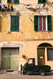 Italian scene with ape car and washing line. Italian car parked in front of a yellow building with green shutters and washing hanging below windows royalty free stock image