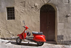Italian scenes. Old red motorcycle parked in Tuscan city center Stock Image