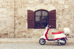 Italian scooter vespa in front of the wall with the window Royalty Free Stock Image