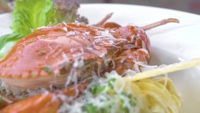 Italian seafood pasta with red crab, fresh herb seasoning and cheese on white plate on wooden table. Serving size. Traditional pasta with seafood in restaurant stock footage