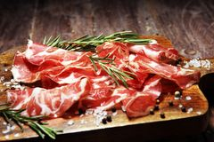 Italian sliced cured coppa with spices. Raw ham. Crudo or jamon with rosemary. Italian sliced cured coppa with spices. Raw ham. Crudo or jamon on wood stock image