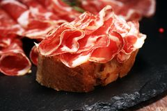 Italian sliced cured coppa with spices. Raw ham. Crudo or jamon with rosemary. Italian sliced cured coppa with spices. Raw ham. Crudo or jamon on wood royalty free stock images