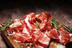 Italian sliced cured coppa with spices. Raw ham. Crudo or jamon with rosemary. Italian sliced cured coppa with spices. Raw ham. Crudo or jamon on wood royalty free stock photos