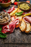 Italian smoked ham Prosciutto with crostini bread and specialties for antipasti on rustic wooden background. Close up Royalty Free Stock Photography