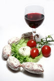 Italian snack. Sausage, tomatoes, salade and red wine isolated on white background royalty free stock images