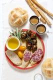 Italian snack lunch. Black Sicilian tomatoes, salami, bread in t Stock Photos