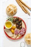 Italian snack lunch. Black Sicilian tomatoes, salami, bread in t Stock Image
