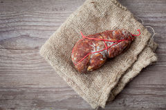 Italian Soppressata. Tasty italian Soppressata ham on wooden background royalty free stock photography