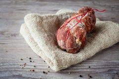 Italian Soppressata. Tasty italian Soppressata ham on wooden background royalty free stock image