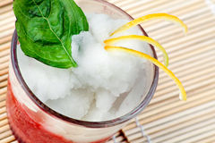 Italian Sorbet. A glass with an italian sorbet of Fruit of the forest and lemon with a leaf of mint and lemon rinds on top Stock Photography