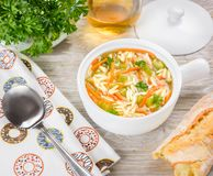 Italian soup with orzo pasta. Chicken orzo soup in a white crock, bowl on wooden background.  Stock Image