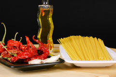 Italian spaghetti. Ingredients for the typical italian spaghetti, aglio, olio, peperoncino: spaghetti made from durum wheat semolina, garlic, chilli pepper and Stock Image