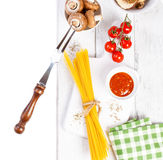 Italian spaghetti, champignon, dry mushrooms, tomato sauce, fresh cherry tomatoes, and spices on a wooden background, pasta ingred Royalty Free Stock Photography