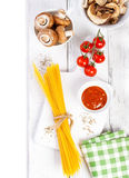 Italian spaghetti, champignon, dry mushrooms, tomato sauce, fresh cherry tomatoes, and spices on a wooden background Royalty Free Stock Image