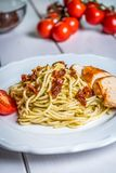 Italian spaghetti with chicken and sundried tomato. Italian pasta spaghetti with chicken, sundried tomato and basil pesto on white table stock image