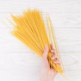 Italian spaghetti in female hands. In white wooden background Stock Photo