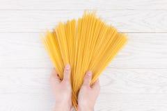 Italian spaghetti in female hands. In white wooden background Stock Image