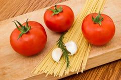 Italian spaghetti ingredients. Spaghetti, tomatoes, garlic and herbs on table royalty free stock photo