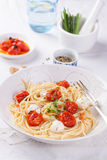 Italian spaghetti pasta with baked cherry tomatoes, mozzarella and spring onions Royalty Free Stock Image