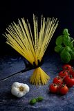 Italian spaghetti pasta with basil, tomatoes and garlic. Italian spaghetti pasta in bunch with basil, tomatoes and garlic. Nice dark background royalty free stock image
